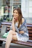 Mujer tranquila morena que se sienta en el banco en calle del verano Foto de archivo
