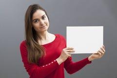 Mujer tranquila 20s que hace un anuncio en la exhibición de un parte movible en blanco al lado de ella Fotos de archivo libres de regalías