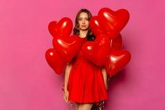 Mujer trastornada con los balones de aire en forma de corazón el día del ` s de la tarjeta del día de San Valentín fotos de archivo