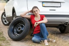 Mujer trastornada de los jóvenes que se sienta en la tierra al lado del coche quebrado en el camino abandonado y para la ayuda qu Foto de archivo libre de regalías
