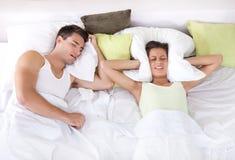 Mujer trastornada en cama con su novio que ronca Imagenes de archivo