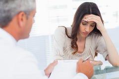 Mujer trastornada que escucha su docter que habla de una enfermedad Imágenes de archivo libres de regalías