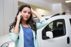Mujer trastornada que llama alguien con su teléfono móvil Fotos de archivo