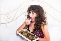 Mujer trastornada que llora y que come los chocolates en dormitorio Imágenes de archivo libres de regalías