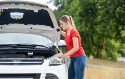 Mujer trastornada que mira debajo del capo del coche recalentado en el fi Fotos de archivo