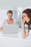 Mujer trastornada que piensa mientras que su amigo enojado la está mirando Imagen de archivo libre de regalías