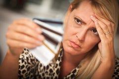 Mujer trastornada que se deslumbra en sus muchas tarjetas de crédito foto de archivo