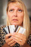 Mujer trastornada que se deslumbra en sus muchas tarjetas de crédito Foto de archivo libre de regalías