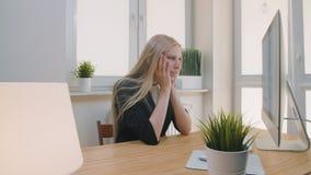 Mujer trastornada que se sienta en el lugar de trabajo Hembra triste rubia en la ropa elegante que agarra la cabeza después de la metrajes