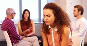 Mujer trastornada que se sienta en silla con los colegas que discuten en fondo
