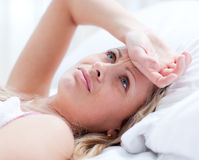 Mujer trastornada que tiene una jaqueca el mentir en una cama Foto de archivo