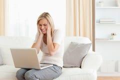 Mujer trastornada que usa una computadora portátil Imágenes de archivo libres de regalías