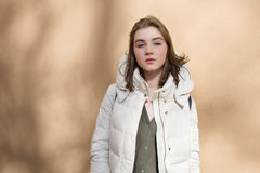 Mujer traviesa hermosa joven de la estación fría en la capa blanca que presenta contra la pared texturizada con el concepto liger Foto de archivo libre de regalías