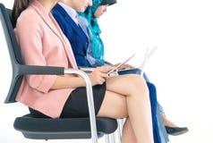 Mujer tres que se sienta en fila aislado en blanco fotos de archivo libres de regalías
