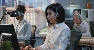 Mujer tres que trabaja en un centro de atención telefónica