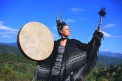 Mujer tribal con los cuernos que juegan un tambor del búfalo en la montaña Imagenes de archivo