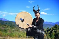 Mujer tribal con los cuernos que juegan un tambor del búfalo en la montaña imagen de archivo libre de regalías