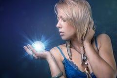 Mujer tribal moderna que sostiene una bola de cristal que brilla intensamente imagenes de archivo