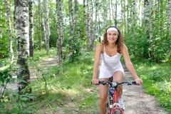 Mujer triguena activa en la bicicleta roja Foto de archivo