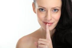 Mujer triguena atractiva atractiva que pone un dedo en sus labios en el fondo blanco Fotos de archivo