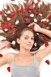 Mujer triguena con los pelos largos y los pétalos color de rosa Fotografía de archivo