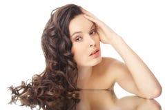 Mujer triguena con los pelos ondulados largos en blanco Imágenes de archivo libres de regalías