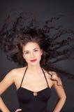 Mujer triguena con su pelo en el movimiento Fotografía de archivo