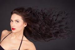 Mujer triguena con su pelo en el movimiento Imagenes de archivo