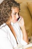 Mujer triguena hermosa con el teléfono móvil en la cama Fotos de archivo libres de regalías