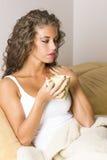 Mujer triguena hermosa joven en la cama con café Imagen de archivo libre de regalías