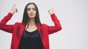 Mujer triguena hermosa joven Vestido en una chaqueta roja Muestra un gesto simbólico de una pistola, un gesto del juego almacen de metraje de vídeo