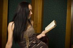 Mujer triguena hermosa que lee un libro Fotografía de archivo libre de regalías