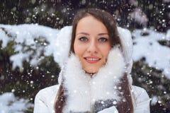 Mujer triguena hermosa que se coloca bajo nevadas Imágenes de archivo libres de regalías