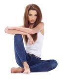 Mujer triguena que se sienta en el piso. Lanzamiento del estudio. Fotos de archivo libres de regalías