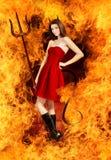 Mujer triguena joven atractiva como diablo en fuego foto de archivo libre de regalías