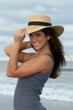 Mujer triguena joven en sombrero de paja en la playa Foto de archivo libre de regalías