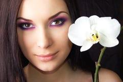 Mujer triguena joven hermosa con la flor de la orquídea Imagen de archivo