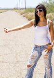 Mujer triguena joven hermosa que hace autostop Foto de archivo libre de regalías