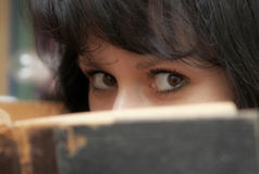 Mujer triguena joven que lee el libro viejo Fotografía de archivo