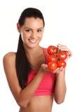Mujer triguena joven que presenta con los tomates Foto de archivo libre de regalías