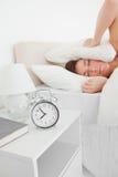 Mujer triguena linda que se despierta con un reloj Imágenes de archivo libres de regalías