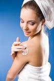 Mujer triguena magnífica del balneario que usa la crema hidratante. Imagen de archivo