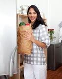 Mujer triguena que desempaqueta el bolso de tienda de comestibles Imágenes de archivo libres de regalías