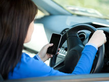 Mujer triguena que usa su teléfono celular mientras que conduce fotos de archivo libres de regalías