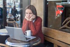 Mujer triste aburrida con el ordenador portátil Imagen de archivo libre de regalías