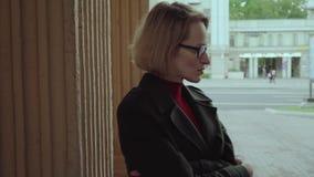 Mujer triste agitada cerca de la pared en la calle de la ciudad almacen de metraje de vídeo