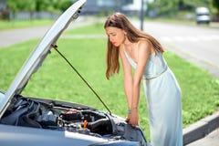 Mujer triste cerca del coche quebrado Imagen de archivo libre de regalías