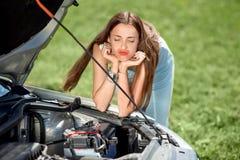 Mujer triste cerca del coche quebrado Fotos de archivo libres de regalías