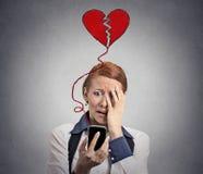 Mujer triste con el corazón quebrado que mira su teléfono móvil Imagen de archivo libre de regalías