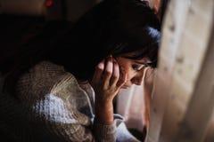 Mujer triste con su cabeza abajo de la mirada a través de la ventana fotos de archivo
